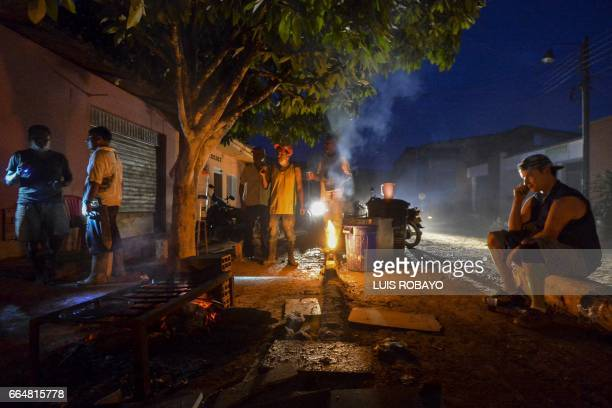 People remain on a street of Mocoa Putumayo department Colombia during a blackout on April 4 2017 Meanwhile looting has become a problem in some...