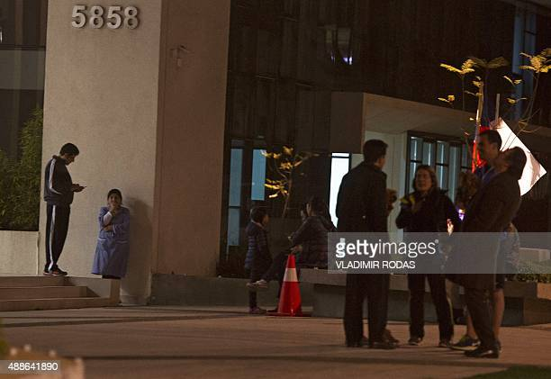 People remain outside a building during a strong quake in Santiago on September 16 2015 A strong 72magnitude earthquake struck the center of Chile on...