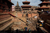 APRIL 27 People remove carvings from the rubble in Patan Durbar Square