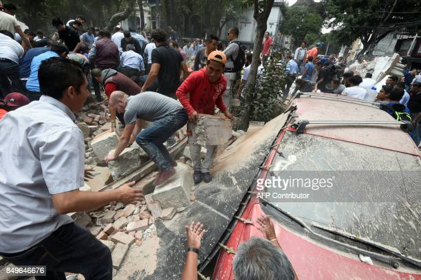 TOPSHOT People remove debris of a building which collapsed after a quake rattled Mexico City on September 19 2017 A powerful earthquake shook Mexico...