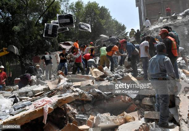 TOPSHOT People remove debris of a collapsed building looking for possible victims after a quake rattled Mexico City on September 19 2017 A powerful...