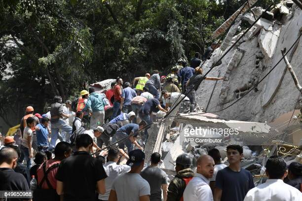 People remove debris of a collapsed building looking for possible victims after a quake rattled Mexico City on September 19 2017 A powerful...