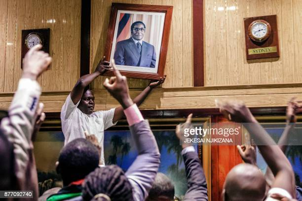 TOPSHOT People remove from the wall at the International Conference centre where parliament had their sitting the portrait of former Zimbabwean...