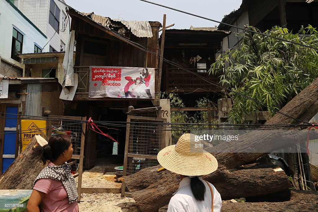 People remove trees destroyed by heavy rain and wind in Myanmar central city Madalay on May 2, 2016. At least eight people killed last week because of violent storms which saw hailstones the size of golf balls rain down across Myanmar after weeks of heatwave temperatures regularly topping 40 degrees. / AFP / STR