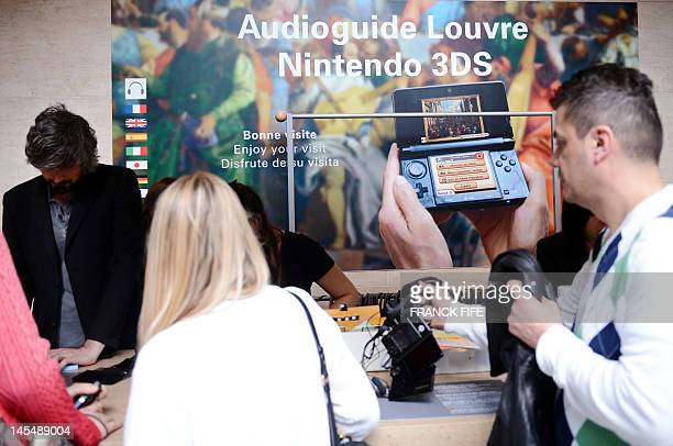 People rent handheld Nintendo 3DS consoles which replace audio guides as they visits the Louvre Museum on April 12 2012 in Paris As part of a...