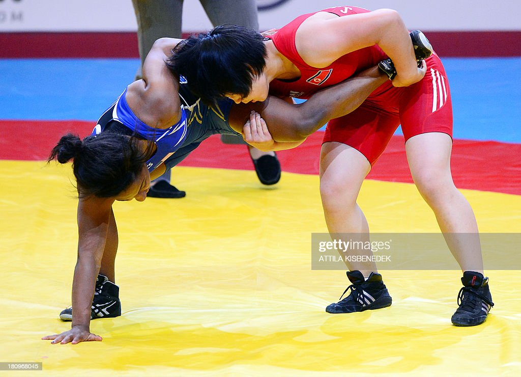 People Republic of Korea's Sim Hyang So (red) and US Victoria Lacey Anthony (blue) fight for the bronze medal during the women's free style 51 kg category of the FILA World Wrestling Championships in Budapest on September 18, 2013. So won te bronze medal. AFP PHOTO / ATTILA KISBENEDEK