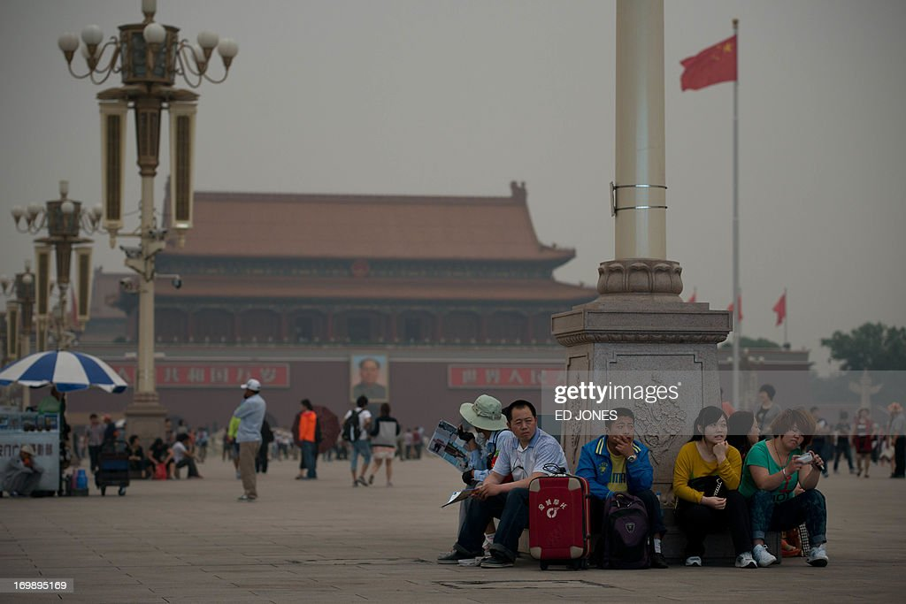 People rest against a lamp post on Tiananmen square in Beijing on June 4, 2013. Authorities launch a major push every June 4 to prevent discussion of the violently crushed 1989 pro-democracy protests, in which at least hundreds of people died. AFP PHOTO / Ed Jones