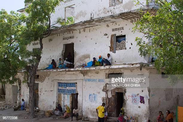 People rest along a bulletridden building in Mogadishu Somalia on November 23 2009 Somalia's embattled president appealed to the international...
