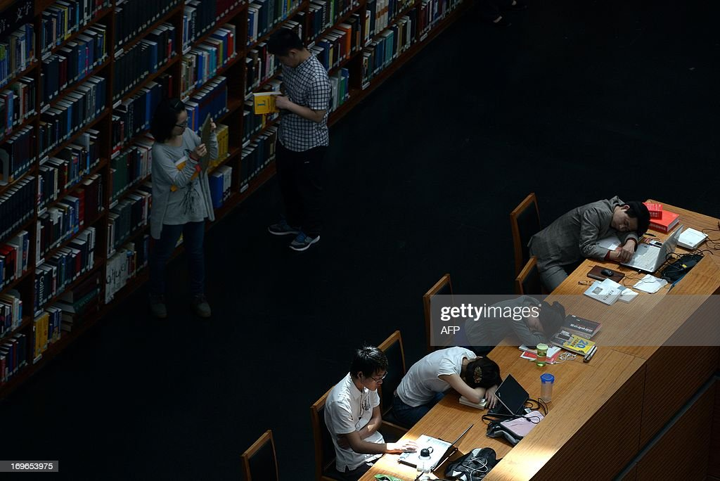 People rest and read books at a national library in Beijing on May 30, 2013. China's ruling Communist Party has called for greater political instruction for young university teachers, the education ministry has said.