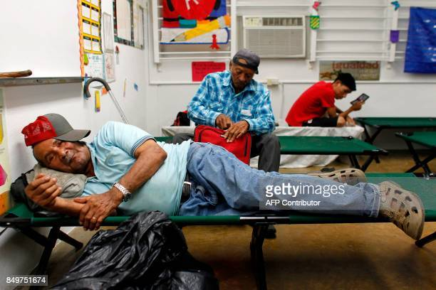 People rest at a shelter as Hurricane Maria approaches Puerto Rico in Fajardo on September 19 2017 Maria headed towards the Virgin Islands and Puerto...