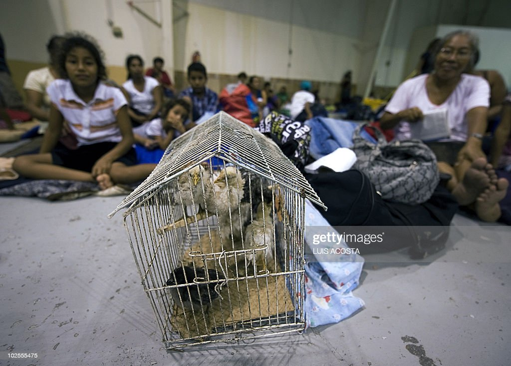 People rest at a shelter next to a cage in Matamoros, Tamaulipas state, Mexico on June 30, 2010. Hurricane Alex was set to make landfall late Wednesday or early Thursday south of the US border with Mexico, possibly as a Category Two hurricane, the Miami-based National Hurricane Center said. AFP PHOTO/Luis Acosta