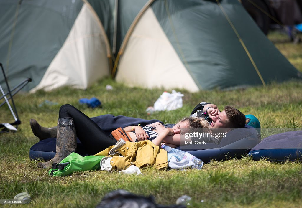 People rest beside their tents as festival goers leave the Glastonbury Festival 2016 at Worthy Farm, Pilton on June 26, 2016 near Glastonbury, England. The Festival, which Michael Eavis started in 1970 when several hundred hippies paid just £1, now attracts more than 175,000 people.