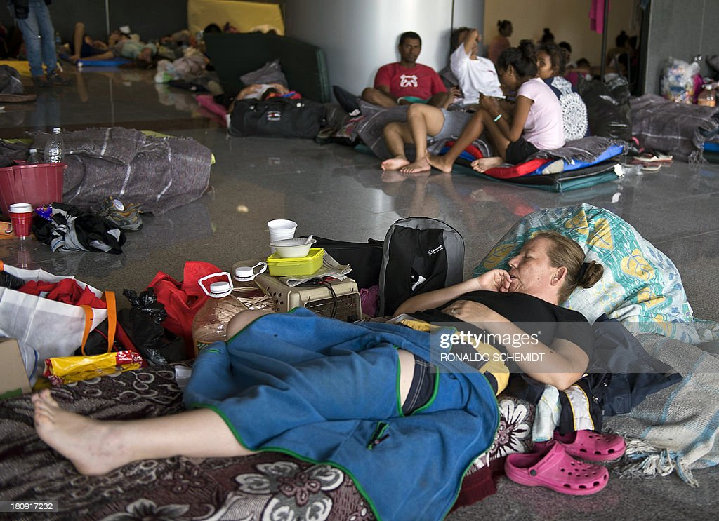 People rest in a shelter in Acapulco, state of Guerrero, Mexico, on September 17, 2013. At least 47 people were killed and thousands evacuated from towns on the Pacific and Gulf of Mexico coasts over the weekend as Tropical Storm Manuel and downgraded Hurricane Ingrid set off landslides and floods that damaged bridges, roads and homes.