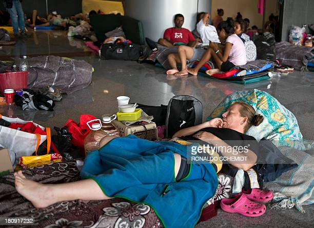 People rest in a shelter in Acapulco state of Guerrero Mexico on September 17 2013 At least 47 people were killed and thousands evacuated from towns...