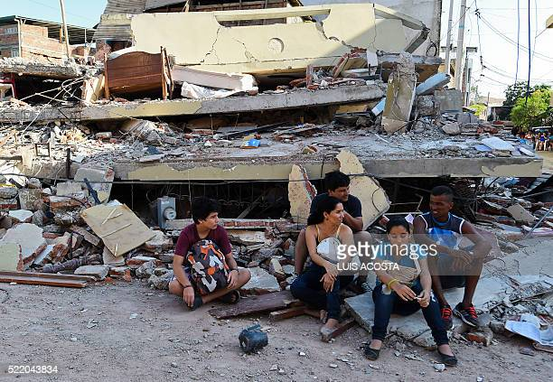 TOPSHOT People rest in front of a destroyed house in Manta Ecuador on April 17 2016 a day after a powerful 78magnitude quake hit the country The toll...