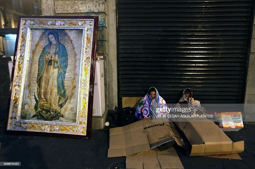 People rest next to an image of the Virgin of Guadalupe while waiting for the passage of Pope Francis in Mexico City on February 13, 2016. Francis became the first pope to enter Mexico's National Palace to meet President Enrique Pena Nieto, as he starts a cross-country tour that will highlight the country's violence and migration troubles. AFP PHOTO / Julio Cesar Aguilar / AFP / Julio Cesar Aguilar Fuentes