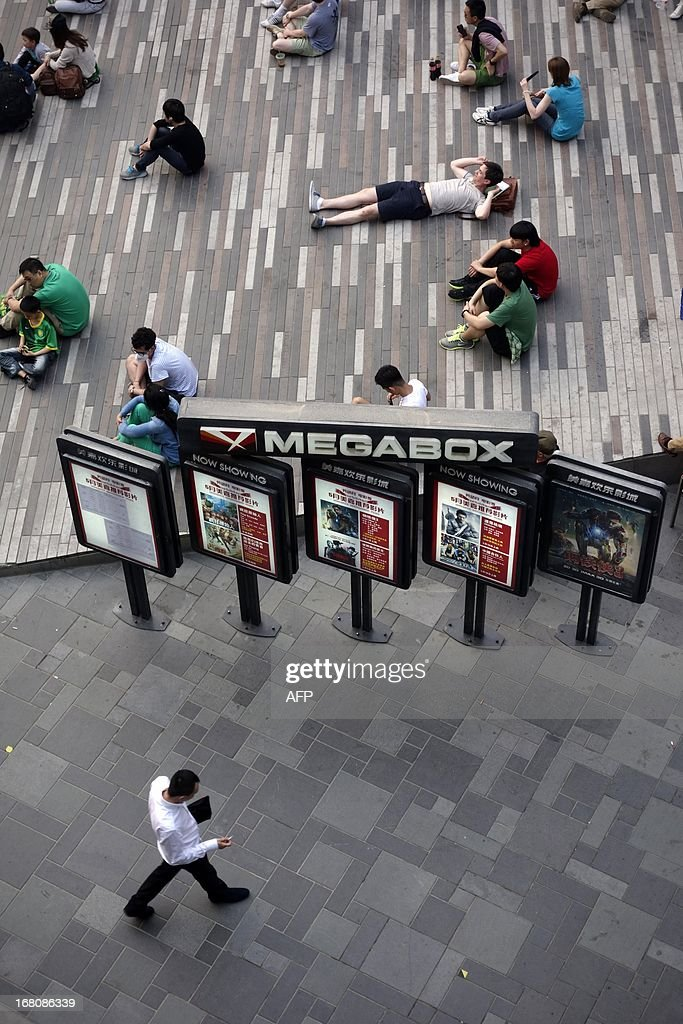 People rest outside a shopping area in Beijing on May 5, 2013. China's economy expanded 7.8 percent in 2012, its slowest pace for 13 years, in the face of weakness at home and in key overseas markets.