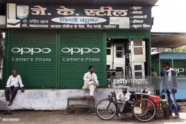People rest outside a shuttered store displaying an advertisement for smartphone maker Oppo Electronics Corp in Gwalior Madhya Pradesh India on...