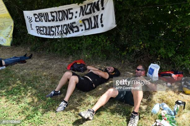 People rest under a sign reading 'Expulsion no requisition yes' during a twoday meeting organised by opponents to a controversial international...