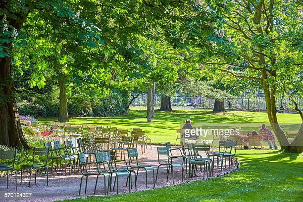 People resting in the sun on chairs in park