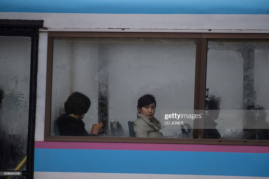 People ride a bus as it passes the 'April 25 Palace', the venue of the 7th Workers Party Congress in Pyongyang on May 6, 2016. North Korea on May 6 kicked off its biggest political show for a generation, aimed at cementing the absolute rule of leader Kim Jong-Un and shadowed by the possibility of an imminent nuclear test. / AFP / Ed Jones