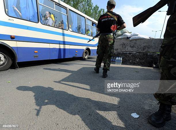 People ride a bus as they pass proRussian fighters of Vostok battalion guarding a checkpoint on the road between Donetsk and Mariupol near the...