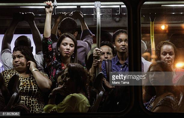 People ride a bus during the evening commute on March 2 2016 in Rio de Janeiro Brazil The government announced that Brazil's economy shrank 38...