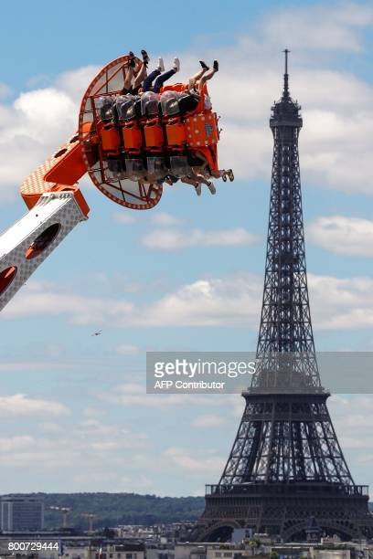 People ride a carnival attraction in the Tuileries Gardens with the Eiffel Tower in the background on June 25 as seen from the rooftop of the Hotel...