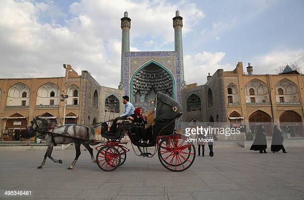 People ride a horse and carriage at sunset in Isfahan's Unescolisted central square on June 2 2014 in Isfahan Iran Isfahan with its immense mosques...
