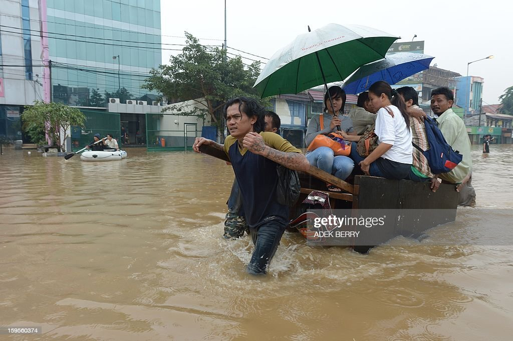 People ride a man pulled cart through a flooded street in Jakarta on January 16, 2013. Floodwaters have inundated 52 subdistricts in Jakarta, claiming one life and displacing some 6,000 residents, according to the National Disaster Mitigation Agency (BNPB).