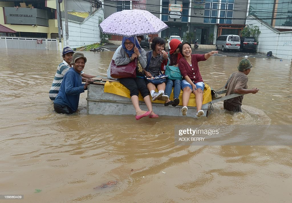 People ride a man pulled cart through a flooded street in Jakarta on January 16, 2013. Floodwaters have inundated 52 subdistricts in Jakarta, claiming one life and displacing some 6,000 residents, according to the National Disaster Mitigation Agency (BNPB). AFP PHOTO / ADEK BERRY