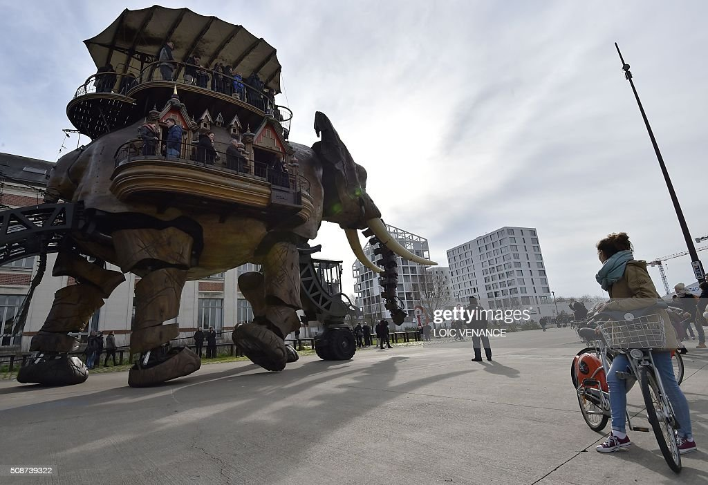 People ride a mechanical elephant made of wood and steel at 'Les Machines de L'Ile' ('Machines of the Isle of Nantes') in Nantes, western France, on February 6, 2016. / AFP / LOIC VENANCE