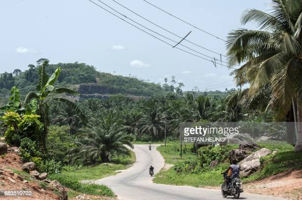 People ride a motorbike by the Obung community on April 26 in Calabar through which the proposed Cross River Super Highway will run and where the...