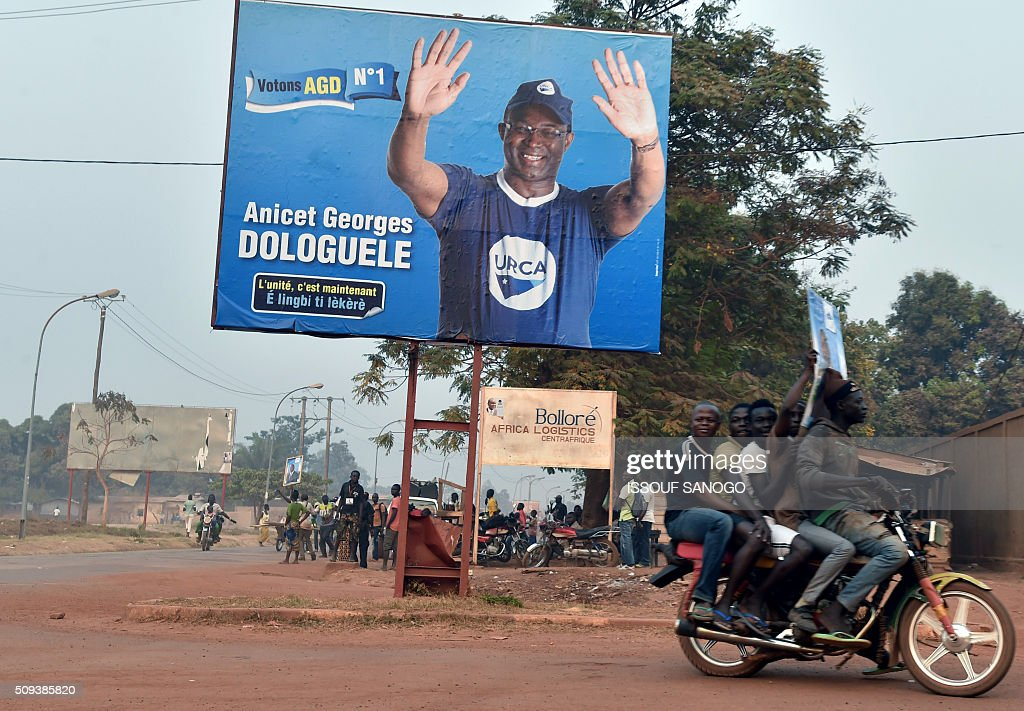 People ride a motorcycle past a campaign poster of Central African Republic second round presidential candidate Anicet Georges Dologuele in a street of Bangui on February 10, 2016, ahead of the Febuary 14 presidential and legislatives elections. The deferred presidential run-off, delayed due to organisational problems, and postponed legislative election, rescheduled after annulment due to irregularities, have been widely seen as turning a page on the worst sectarian violence in the traditionally unstable and dirt poor nation. / AFP / ISSOUF SANOGO