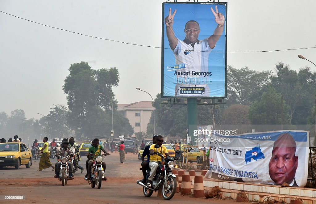 People ride a motorcycle past a campaign posters of Central African Republic second round presidential candidate Anicet Georges Dologuele and Faustin Archange Touadera in a street of Bangui on February 10, 2016, ahead of the Febuary 14 presidential and legislatives elections. The deferred presidential run-off, delayed due to organisational problems, and postponed legislative election, rescheduled after annulment due to irregularities, have been widely seen as turning a page on the worst sectarian violence in the traditionally unstable and dirt poor nation. / AFP / ISSOUF SANOGO