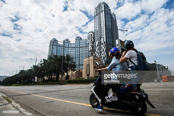 People ride a motorcycle past the Studio City casino resort developed by Melco Crown Entertainment Ltd in Macau China on Tuesday Oct 27 2015 Studio...