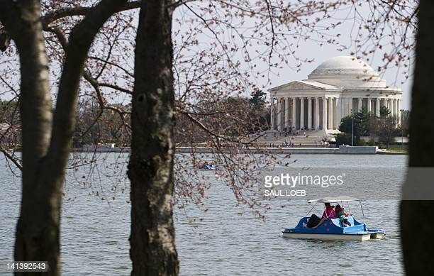 People ride a paddleboat as cherry blossom trees begin to bloom adjacent to the Tidal Basin and Jefferson Memorial on the National Mall in Washington...