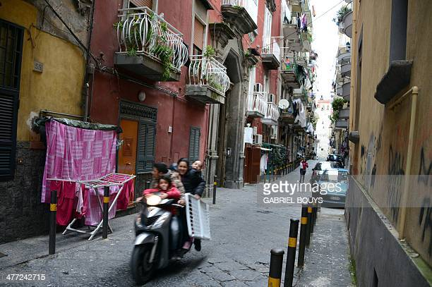 People ride a scooter in a street of Naples on March 7 2014 AFP PHOTO / GABRIEL BOUYS
