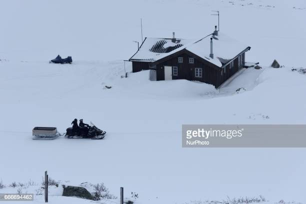 People ride a snowmoblie in the village Finse along the OsloBergen train route on March 04 2017 The village sits at an elevation of 1222 metres above...