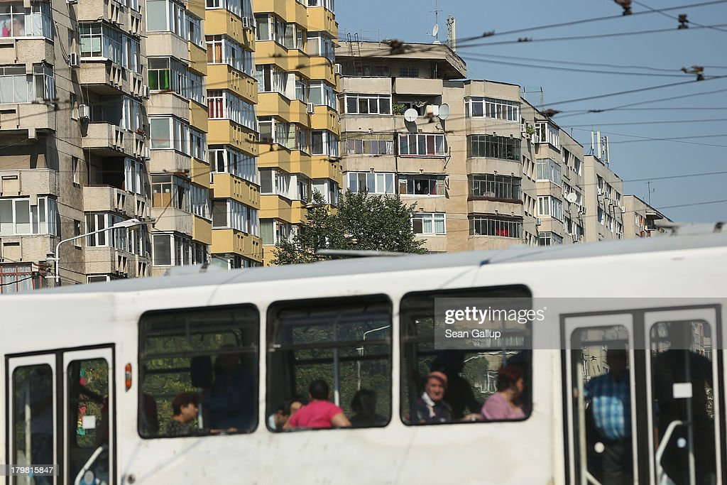 People ride a tram as communist-era apartment buildings loom behind in Titan district on September 7, 2013 in Bucharest, Romania. While Romania's economic output has risen significantly since it joined the European Union in 2007, it still lags in infrastructure development and the fight against corruption.