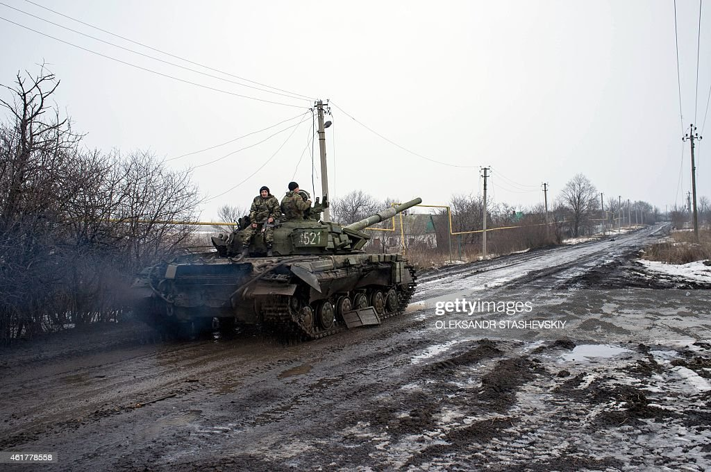 People ride a Ukrainian tank past a damaged vehicle in the village of Tonenke some 5 kilometers from the Donetsk airport on January 19 2015 Sporadic...