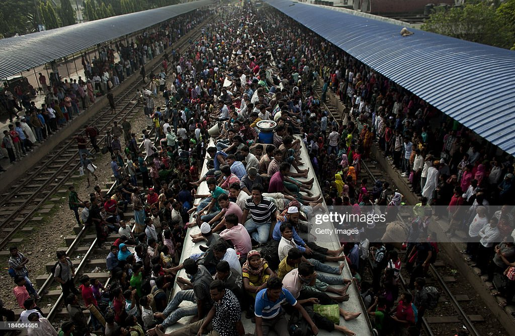 People ride an overflowing train at a railway station on October 15, 2013 in Dhaka, Bangladesh. Eid Al-Adha, known as the 'Feast of the Sacrifice', is one of the most significant festivals on the Muslim calendar. The holiday marks the end of the Haji Pilgrimage and serves as day to remember the Islamic profit Ibrahim, and his willingness to sacrifice his son to God. On this day, Muslims in countries around the world start the day with prayer and spend time with family, offer gifts and often give to charity. It is customary for Muslims family to honour Allah by sacrificing a sheep or goat and sharing the meat amongst family members.