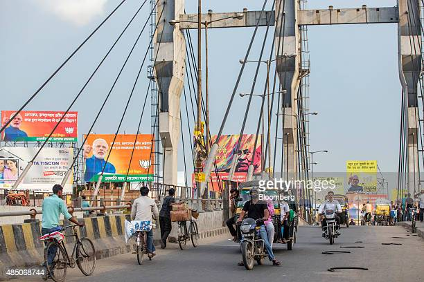 People ride bicycles and autorickshaws over a bridge past election billboard advertisements featuring images of Indian Prime Minister Narendra Modi...