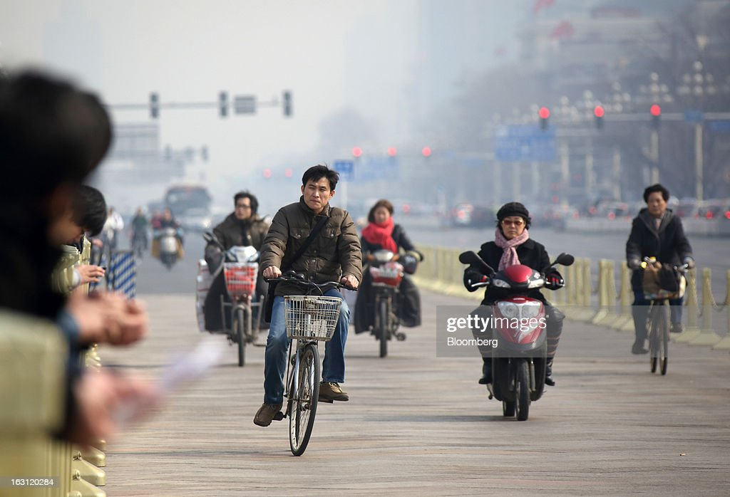 People ride bicycles and motorcycles near Tiananmen Square in Beijing, China, on Tuesday, March 5, 2013. China maintained its economic-growth target at 7.5 percent for 2013 while setting a lower inflation goal of 3.5 percent, setting up a challenge for new leaders to keep prices in check without harming expansion. Photographer: Tomohiro Ohsumi/Bloomberg via Getty Images