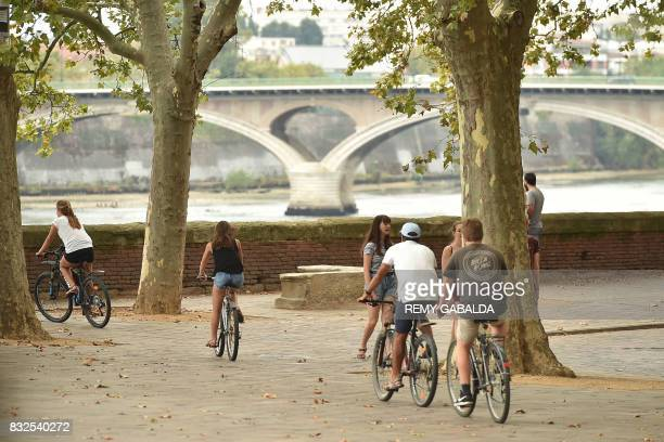 People ride bicycles as others walk in Toulouse on August 16 2017 / AFP PHOTO / REMY GABALDA
