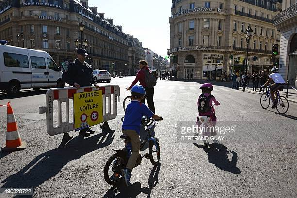 People ride bicycles at Place de l'Opera during the 'CarFree Day' event in Paris on September 27 2015 as part of the French capital's leadup to...