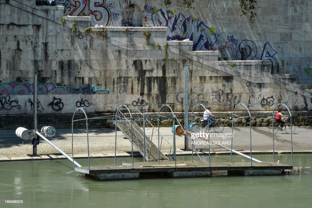 People ride bicycles in front of a Boarding pier and shores dotted with waste at the entrance of 'Ships of Rome', the tourist service navigation on the Tiber, in central Rome, on May 9, 2013. Tourists cruises along Rome's Tiber River have been suspended indefinitely for the first time since they began a decade ago because the waterway is judged too dirty.