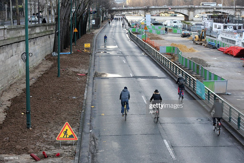 People ride bicycles on the express road way next to the river Seine on January 27, 2013 in the center of Paris. This express way will be closed on January 28 for construction work.