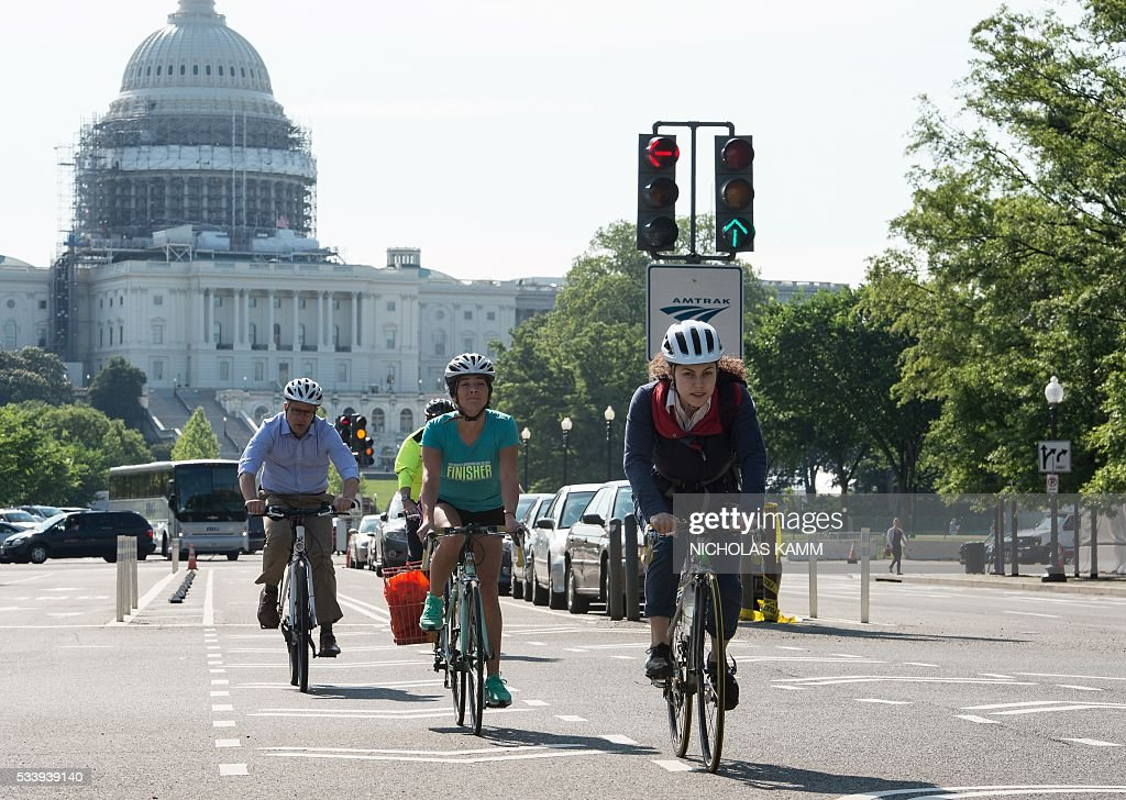 People ride bicycles past the US Capitol in Washington, DC, on May 24, 2016. / AFP / Nicholas Kamm