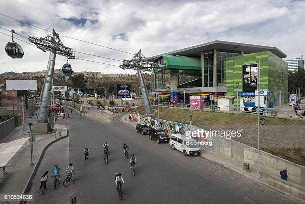 People ride bicycles underneath the Mi Teleferico cable car green line station in La Paz Bolivia on Sunday Sept 4 2016 Boliva's Mi Teleferico cable...